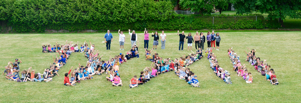 Students and staff spell out JXXIII on the grass outside