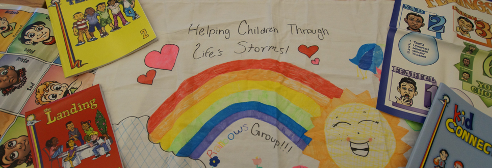 "Poster decorated with a rainbow, sun and hearts, with the phrase, ""Helping Children Through Life's Storms"""