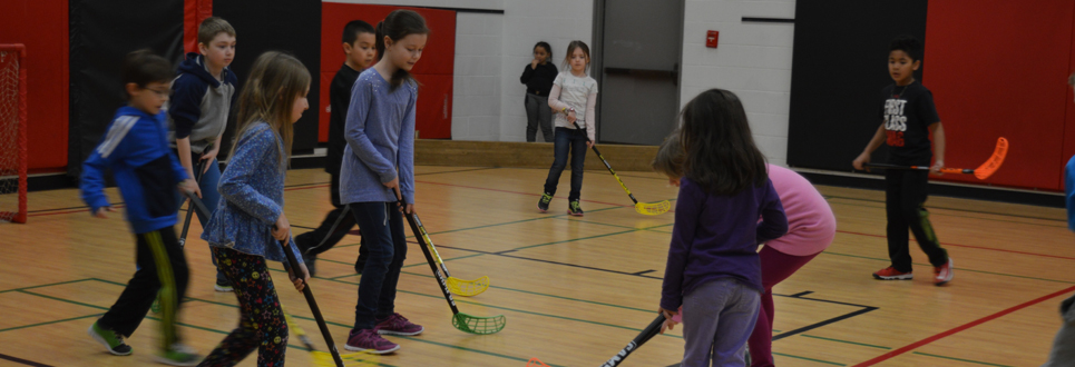 A group of students playing hockey in the school gym.